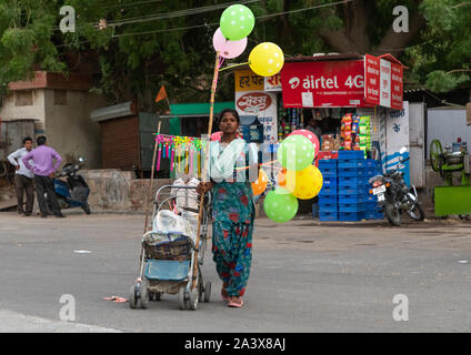 Indian woman with a stroller selling balloons in the street, Rajasthan, Bikaner, India - Stock Photo