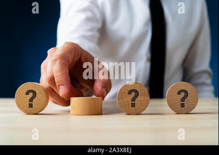 Businessman placing four wooden circles with question mark on them in a row in a conceptual image. - Stock Photo