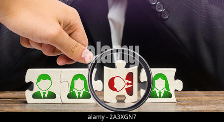 A magnifying glass looks at a businessman sitting in despair over the not assembled puzzles symbolizing a team of employees. Toxic or incompetent work - Stock Photo
