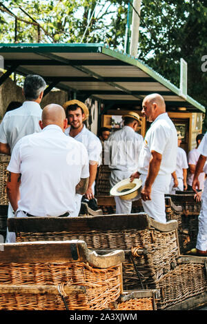 Monte, Madeira, Portugal - Sep 14 2019: Wicker Basket Sledges, blurred drivers, Carreiros do Monte. in background. Traditional transport to Funchal, now tourist attraction. Straw hats, white clothes. - Stock Photo