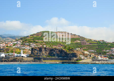 Picturesque small fisherman village Camara de Lobos in Madeira Island, Portugal photographed from the waters of the Atlantic ocean. Small city on a hill by the coast. Banana plantation on the slopes. - Stock Photo
