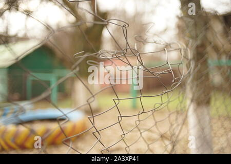 Old bent mesh fence. Selective focus. Autumn mood. - Stock Photo