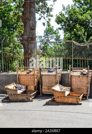 Monte, Madeira, Portugal - Sep 14, 2019: Wicker Basket Sledges. Historical mean of transport between Monte and Funchal, now ride as a tourist attraction. Typical straw hats of the Carreiros drivers. - Stock Photo