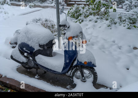 Denver, Colorado, USA- October 10, 2019: Scooter covered in snow during Denver's first snow storm of the season. - Stock Photo