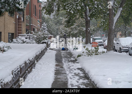Denver, Colorado, USA- October 10, 2019: Man cleans side walk at Capitol Hill neighborhood during Denver's first snow storm of the season. - Stock Photo