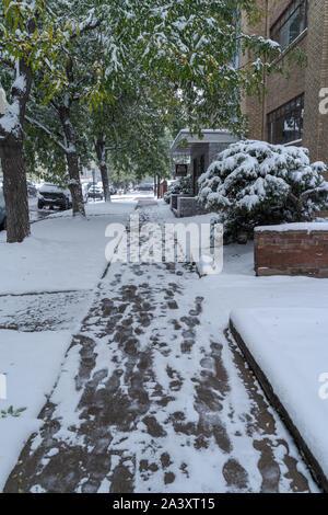 Denver, Colorado, USA- October 10, 2019: snow covered side walk during Denver's first snow storm of the season. - Stock Photo