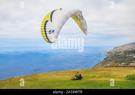 Arco da Calheta, Madeira, Portugal - Sep 16, 2019: Tandem paragliders landing on a grass on the cliffs above the Atlantic ocean. Madeiran landscape in background. Paragliding, active vacation. - Stock Photo