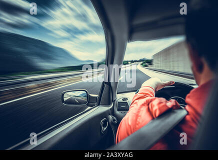 The driver of the car rushes along the highway. - Stock Photo