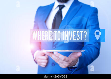 Writing note showing Where To Invest Question. Business concept for asking someone about place to put money into Businessman in blue suite with a tie - Stock Photo