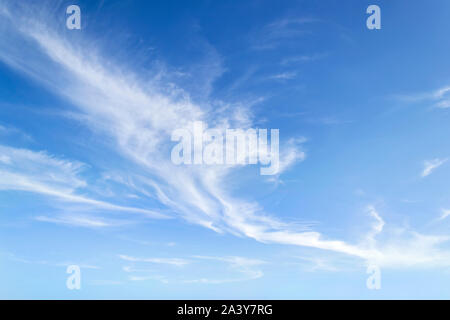 Translucent airy cirrus clouds high in a blue sky. Cloud species and varieties. Atmospheric phenomena. Skyscape on a sunny day. Beauty in nature. - Stock Photo