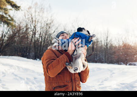 Pug dog walking with his master. Man playing with his pet and having fun. Puppy wearing winter coat.
