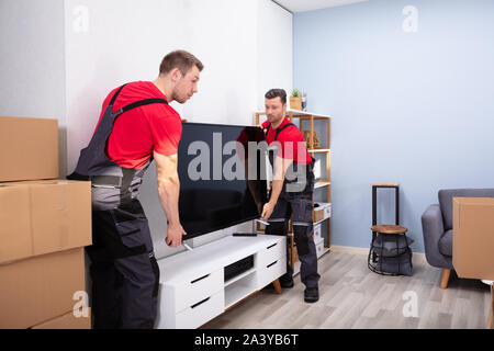 Two Male Professional Movers In Uniform Unloading LCD Television In The Living Room - Stock Photo