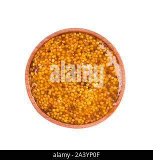 Whole grain Dijon mustard in wooden bowl with brown seeds. Macro food photo close up, isolated on white background. - Stock Photo