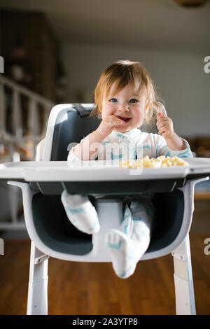 Baby girl eating in high chair