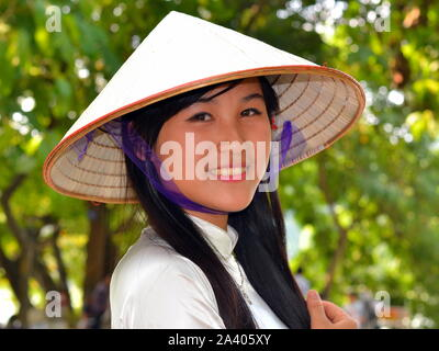 Beautiful, young Vietnamese woman wearsan elegant Asian conical straw hat (nón lá) with blue silk chin strap and smiles for the camera. - Stock Photo