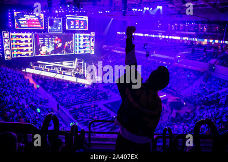 Big esports event. Video games fan on a tribune at tournament's arena with hands raised. Cheering for his favorite team - Stock Photo