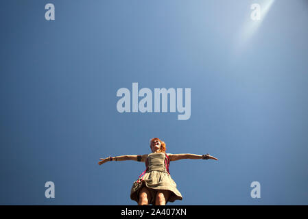 Rio de Janeiro, Brazil - February  09, 2016: Girl walking with stilts, arms wide open under the sunlight and clear blue sky, during Rio Carnival - Stock Photo