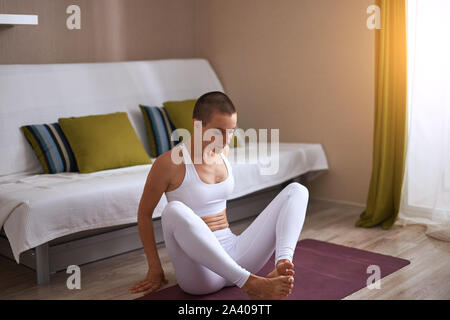 Woman with crossed legs going to stretch at home, leg muscles. - Stock Photo