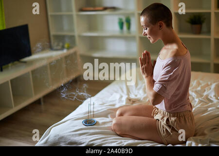 Peaceful girl in pajamas meditating at morning while sitting on bed with burning aroma incense sticks in hands. Praying pose. Meditation, yoga concept