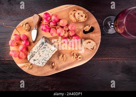 Gorgonzola cheese, shot from above on a dark rustic wooden background with wine and copy space - Stock Photo