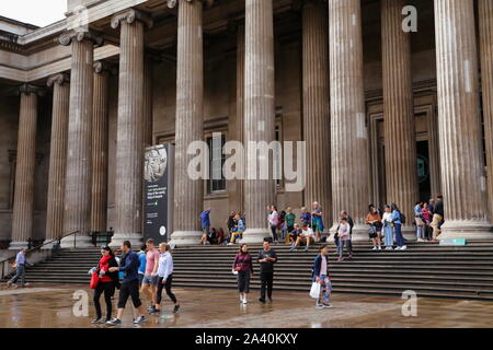 People outside South entrance of the British Museum in London, United Kingdom, on a rainy afternoon during the summer. - Stock Photo