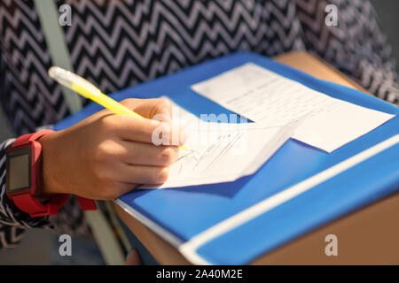 Close up of girl writing the address before sending parcel - Stock Photo
