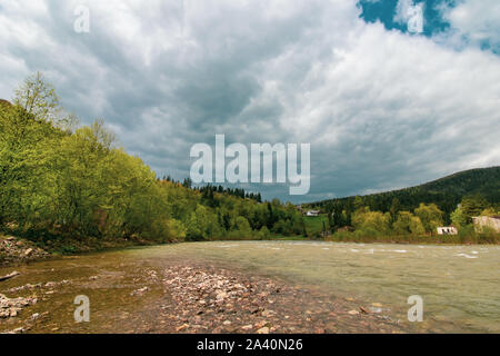 River in the mountains. Beautiful landscape of Carpathians in Ukraine. Yaremche. Thundercloud, storm clouds. Travel background. Pine forest, pinewood. - Stock Photo