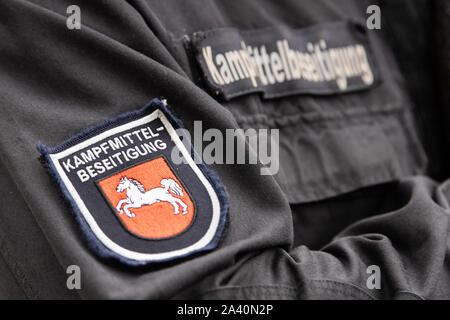 11 October 2019, Lower Saxony, Göttingen: A blaster wears uniforms with the inscription 'Kampfmittelbeseitigung' and the Niedersachsen-Ross. After a possible bomb discovery near the shooting range, about 14 000 people will be evacuated on 12.10.2019. Photo: Swen Pförtner/dpa - Stock Photo