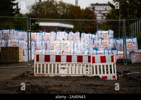 11 October 2019, Lower Saxony, Göttingen: A sign 'Attention, explosive ordnance clearance. Danger to life. Trespassing forbidden' can be seen in front of sandbags behind a barrier at the presumed location of a world war bomb at the 'Schützenanger'. After a possible bomb discovery near the shooting range, about 14 000 people will be evacuated on 12.10.2019. Photo: Swen Pförtner/dpa - Stock Photo