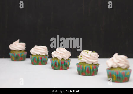 Green cupcakes with cream hat in multi-colored papers on a white table on a dark background. Focus on cake, depth of field effect - Stock Photo