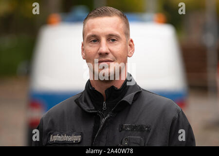 11 October 2019, Lower Saxony, Göttingen: Thorsten Lüdeke, explosives master of the explosive ordnance disposal service, stands in front of an emergency vehicle. After a possible bomb discovery near the shooting range, about 14 000 people will be evacuated on 12.10.2019. Photo: Swen Pförtner/dpa - Stock Photo