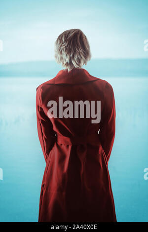Blonde woman standing by lake - Stock Photo