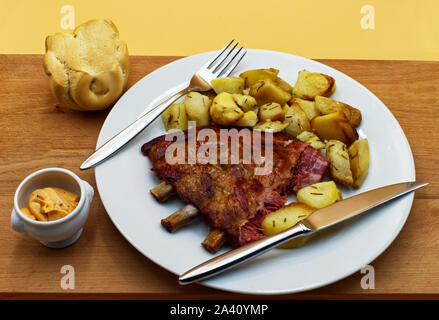 Grilled spare pork ribs with roasted potatoes, bread and sauce, on wooden table - Stock Photo
