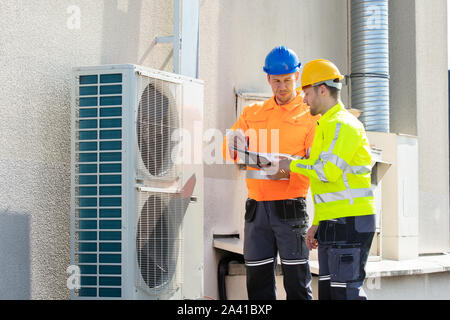 Two Electricians Men Wearing Safety Jackets Checking Air Conditioning Unit On Building Rooftop - Stock Photo