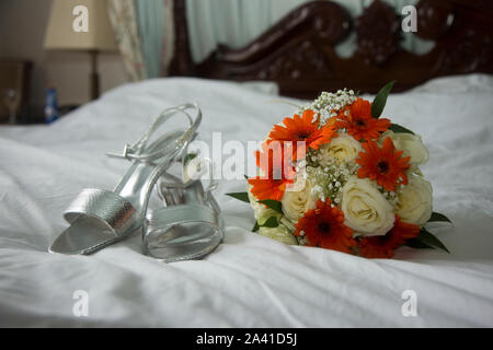 Brides bouquet and shoes on her wedding day, shot as a still life on the bed, before the wedding, no people - Stock Photo