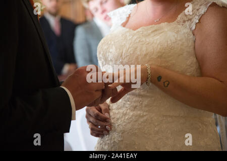 Bride and groom close up of their hands as they exchange rings on their wedding day, no faces are seen in this image, wedding day exchange of rings - Stock Photo