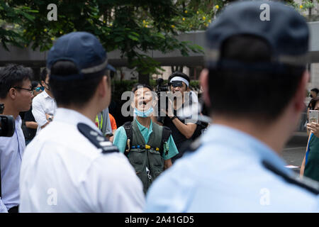 Hong Kong. 11th October 2019. Lunchtime flash mob demonstration by Pro-democracy demonstrators in Chater Square , Central District in Hong Kong. The protestors gathered to protest about treatment of those arrested by the police during Pro-democracy protests in the last 4 months. Police threatened to stop demonstration but it passed peacefully and concluded with march through city streets . Pic. Protestor shouts at police. Iain Masterton/Alamy Live News. - Stock Photo