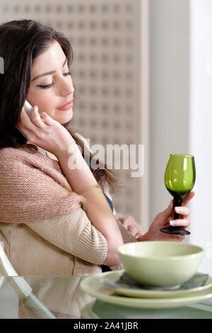 Beautiful young woman chatting on her mobile phone in her kitchen - Stock Photo