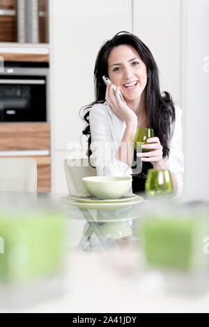 Attractive young woman talking on the phone in her kitchen - Stock Photo