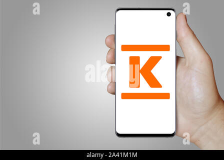 A man holds a phone displaying the logo of company Kesko listed on OMX Helsinki. Grey gradient background. Credit: PIXDUCE - Stock Photo