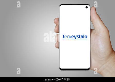 A man holds a phone displaying the logo of company Terveystalo listed on OMX Helsinki. Grey gradient background. Credit: PIXDUCE - Stock Photo