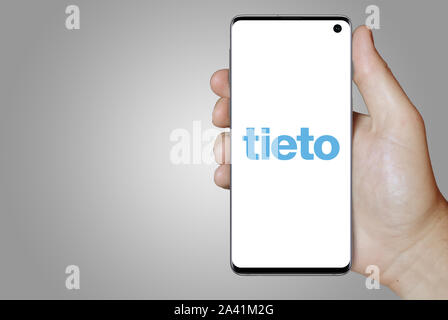 A man holds a phone displaying the logo of company Tieto listed on OMX Helsinki. Grey gradient background. Credit: PIXDUCE - Stock Photo