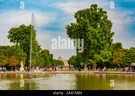 Nice close view of the octagonal lake 'Bassin Octogonal' with fountain and green chairs in the popular Tuileries Garden in Paris. The avenue with two... - Stock Photo