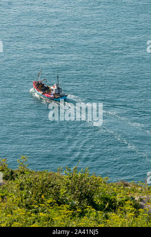 A small inshore fishing boat or trawler of the coast at sea on the Isle of Wight. Fishermen going to sea to catch. - Stock Photo