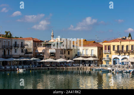 Venetian Harbour with small fishing boats and waterfront restaurants in Rethymno, Crete - Stock Photo