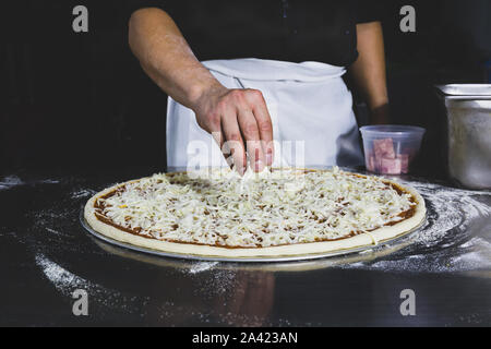 Chefs hand putting cheese on the pizza in black background. - Stock Photo