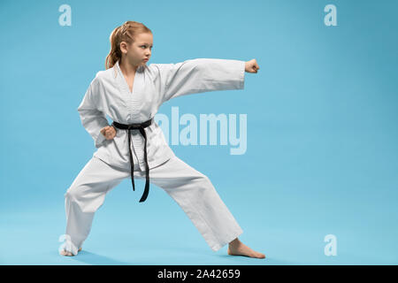 Pretty, young girl practicing karate and jujitsu. Confident junior wearing in white kimono with black belt standing in stance. Concept of wellness and martial arts. - Stock Photo