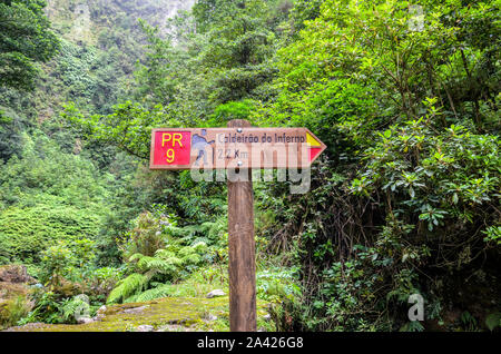 Information tourist sign giving directions and distances on a hiking trail Caldeirao de Inferno, Madeira island, Portugal. Levada walking on Portuguese island. Green forest in the background. Tourism. - Stock Photo