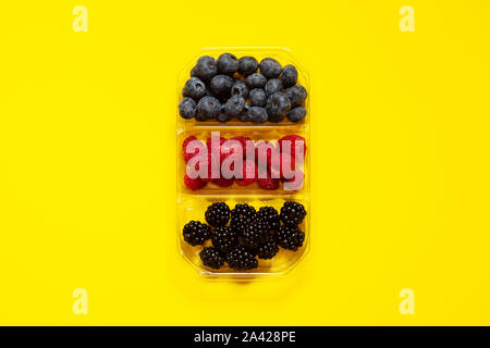 Flatlay group of fresh blueberries, raspberries and blackberries in a transparent plastic container isolated in a yellow background viewed from the to - Stock Photo