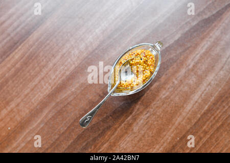 mustard in a glass bowl. French grain mustard in a bowl. French grain mustard in a glass bowl on white wooden table - Stock Photo